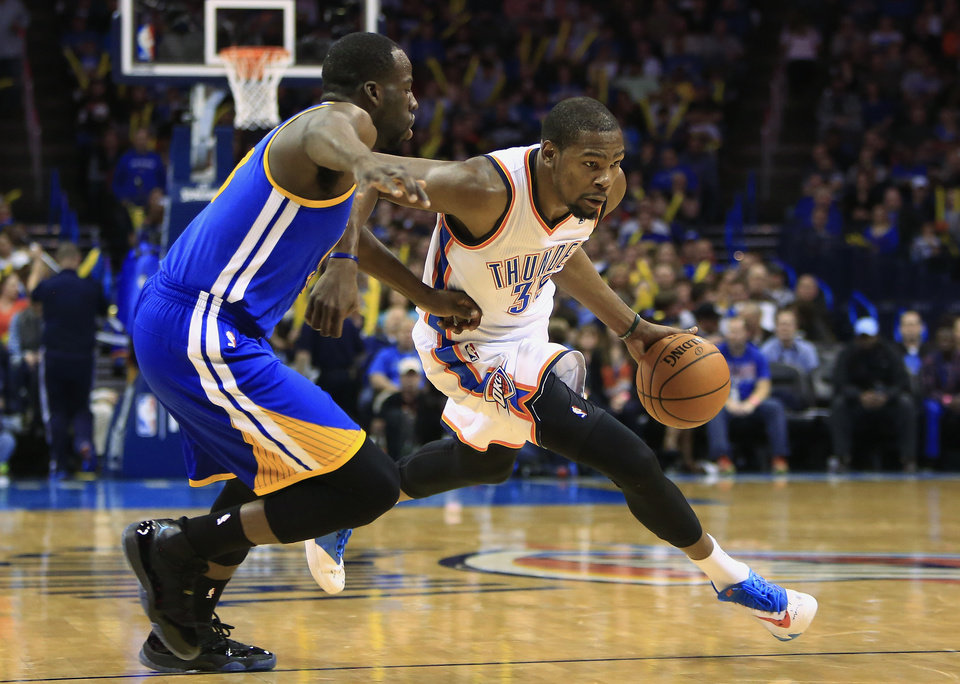 Photo - Oklahoma City Thunder small forward Kevin Durant (35) drives to the basket as Golden State Warriors small forward Draymond Green (23)  defends during the fourth quarter of an NBA basketball game Friday, Jan. 17, 2014, in Oklahoma City. (AP Photo/Alonzo Adams)
