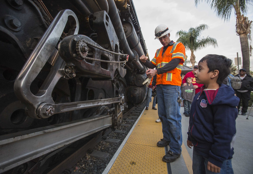 Photo - Miguel Angel Warner, right, 4, of Los Angeles, asks Ed Dickens, left, senior manager of  Heritage Operations about the historic locomotive, Union Pacific Big Boy No. 4014 at Metrolink Station, Sunday, Jan. 26, 2014, in Covina, Calif. The locomotive will head for Colton over the next several weeks before No. 4014 departs for Union Pacific's Heritage Fleet Operations headquarters in Cheyenne, Wyo. (AP Photo/Ringo H.W. Chiu)