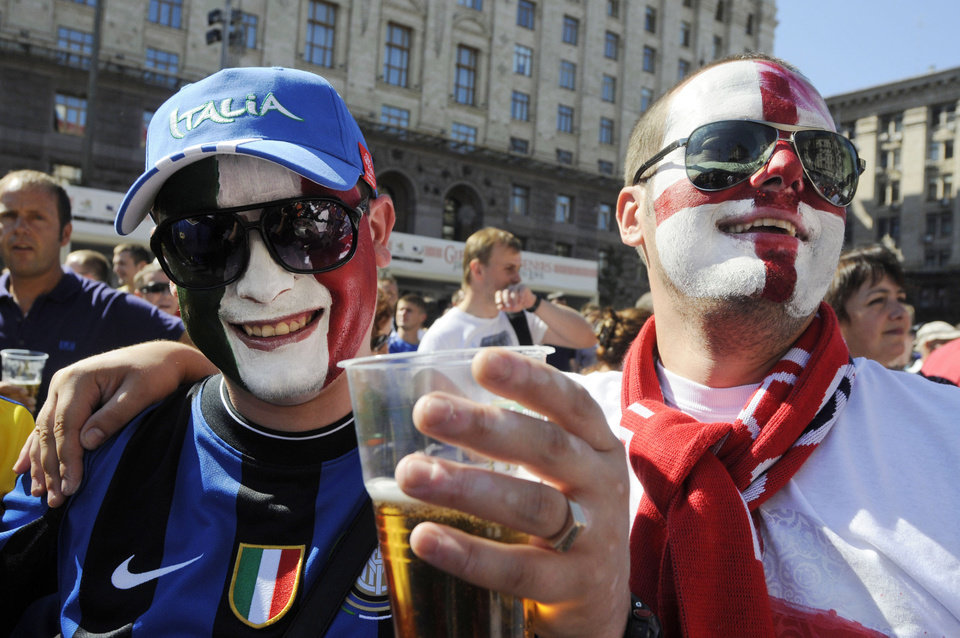 An Italian soccer fan and an England soccer fan wait for the start of the Euro 2012 soccer championship quarterfinal match between England and France at the Fan Zone in Kiev Ukraine, Sunday, June 24, 2012. (AP Photo/Sergei Chuzavkov)