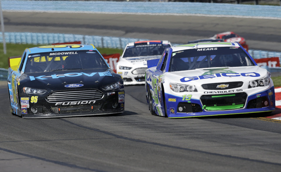 Photo - Michael McDowell (95) and Casey Mears (13) battle for position in the esses during a NASCAR Sprint Cup Series auto race at Watkins Glen International, Sunday, Aug. 10, 2014, in Watkins Glen, N.Y. (AP Photo/Mel Evans)