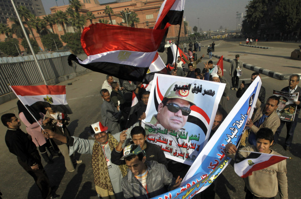 Photo - Egyptians shout anti-terrorism slogans and wave national flags as they hold a poster of Egypt's Defense Minister, Gen. Abdel-Fattah el-Sissi in Tahrir Square, the epicenter of the 2011 uprising, in Cairo, Egypt, Saturday, Jan. 25, 2014. Demonstrators began gathering Saturday in Egypt's Tahrir Square to mark the third anniversary of the start of its 2011 revolution, though streets remained empty elsewhere in a city on edge following a spate of bombings claimed by militants. The interim government has blamed the Muslim Brotherhood group for the violence and designated it as a terrorist organization while the group denied any links to terrorism. Arabic reads,