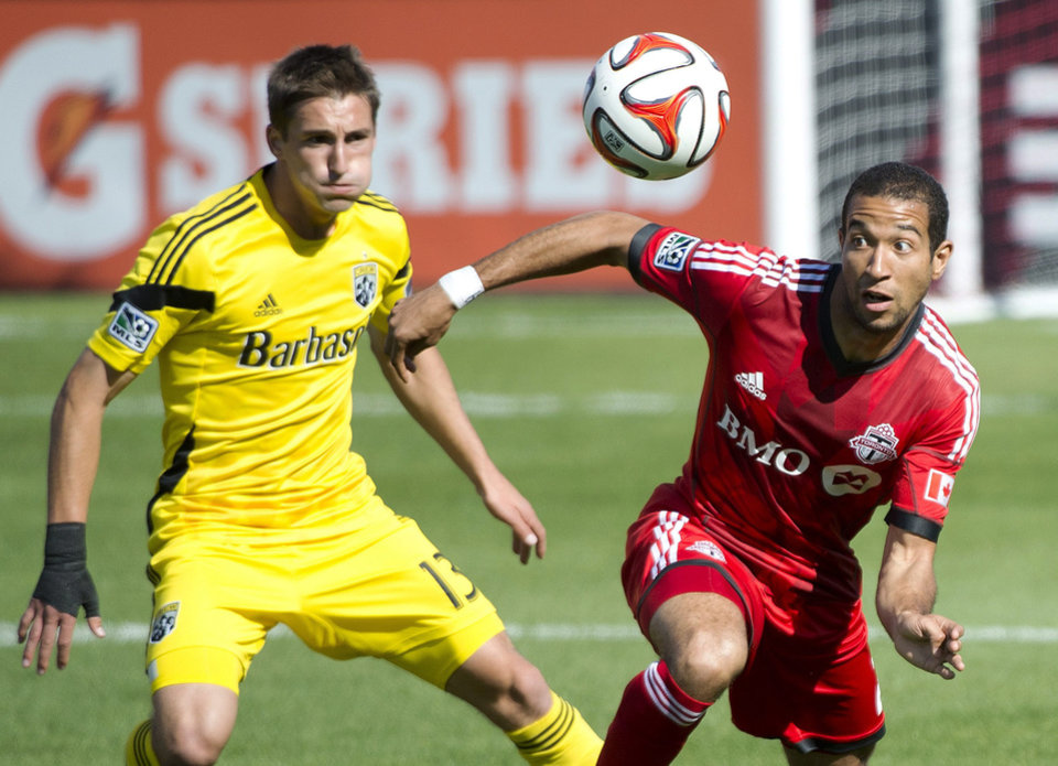 Photo - Toronto FC defender Justin Morrow, right, eyes the ball next to Columbus Crew midfielder Ethan Finlay during the first half of an MLS soccer game in Toronto on Saturday, May 31, 2014. (AP Photo/The Canadian Press, Nathan Denette)