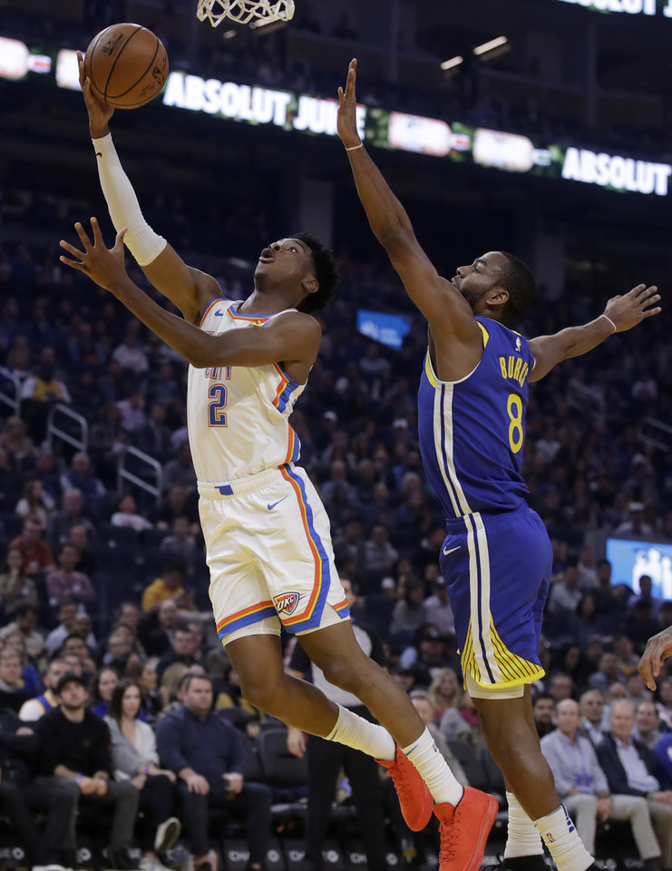 Photo - Oklahoma City Thunder guard Shai Gilgeous-Alexander, left, lays up a shot past Golden State Warriors' Alec Burks (8) in the first half of an NBA basketball game Monday, Nov. 25, 2019, in San Francisco. (AP Photo/Ben Margot)