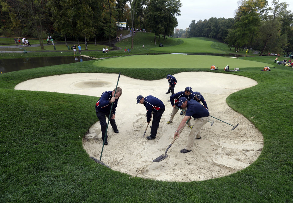Photo - Grounds crew members work in a bunker on the ninth hole following a rain delay during the foursome matches at the Presidents Cup golf tournament at Muirfield Village Golf Club Friday, Oct. 4, 2013, in Dublin, Ohio. (AP Photo/Darron Cummings)