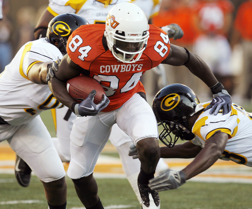 Photo - OSU's Hubert Anyiam (84) tries to break away from a pair of Grambling defenders during the college football game between the Oklahoma State University Cowboys (OSU) and the Grambling State University Tigers (GSU) at Boone Pickens Stadium in Stillwater, Okla., Saturday, September 26, 2009. Photo by Nate Billings, The Oklahoman ORG XMIT: KOD