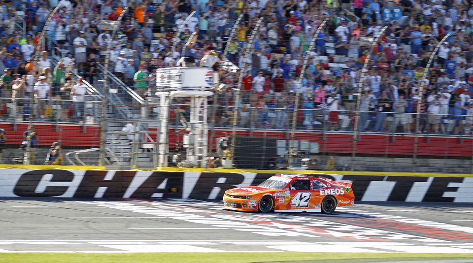 Photo - Kyle Larson (42) takes the checkered flag to win the NASCAR Nationwide series History 300 auto race at Charlotte Motor Speedway in Concord, N.C., Saturday, May 24, 2014. (AP Photo/Terry Renna)
