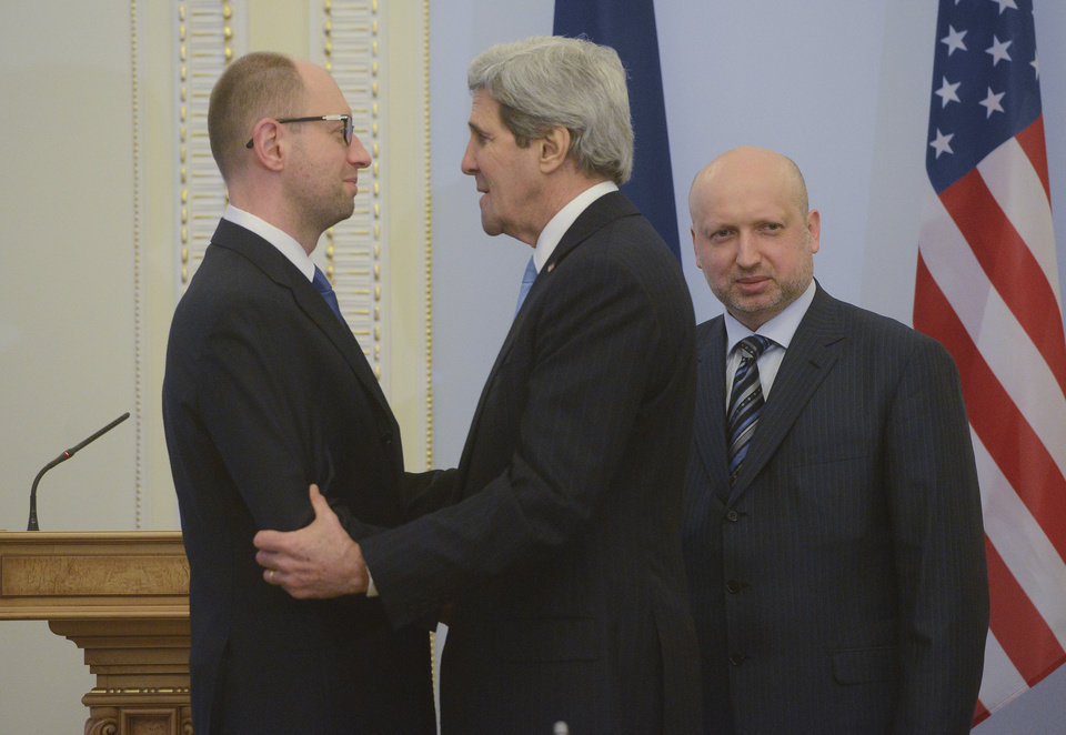 Photo - U.S. Secretary of State John Kerry, center,  greets Ukrainian Prime Minister Arseniy Yatsenyuk, left, parliament speaker Oleksandr Turchynov is seen right prior their meting in Kiev, Ukraine, Tuesday, March, 4, 2014.  In a somber show of U.S. support for Ukraine's new leadership, Secretary of State John Kerry walked the streets Tuesday where nearly 100 anti-government protesters were gunned down by police last month, and promised beseeching crowds that American aid is on the way.  The Obama administration announced a $1 billion energy subsidy package in Washington as Kerry was arriving in Kiev. (AP Photo/Andrew Kravchenko, pool)