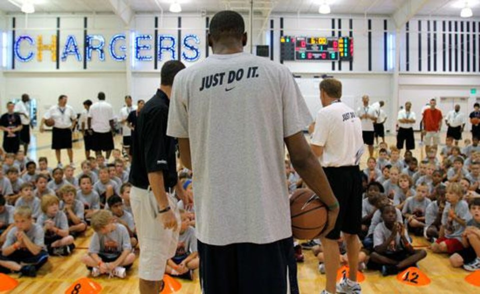 Photo -  Kevin Durant stands in front of camp participants during the second day of the Kevin Durant basketball camp at Heritage Hall in Oklahoma City, Thursday, June 30, 2011.  Photo by Garett Fisbeck, The Oklahoman