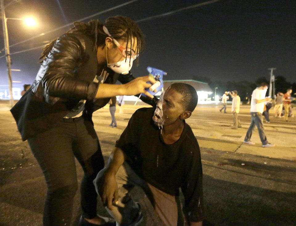 Photo - A man is helped ease the effects of tear gas during a protest Monday, Aug. 18, 2014, for Michael Brown, who was killed by a police officer Aug. 9 in Ferguson, Mo. Brown's shooting has sparked more than a week of protests, riots and looting in the St. Louis suburb. (AP Photo/Charlie Riedel)