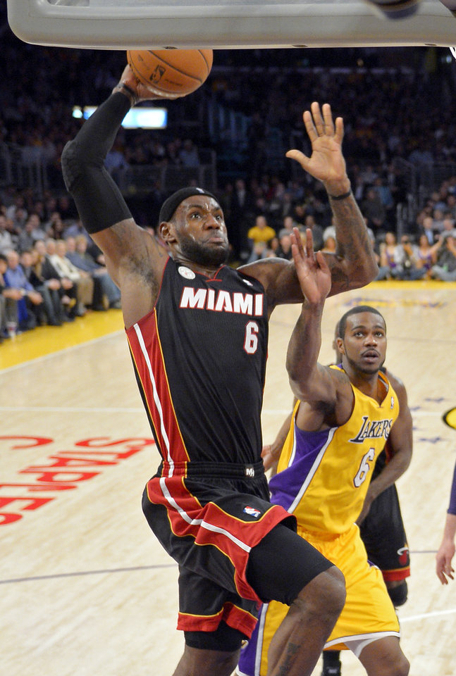 Miami Heat forward LeBron James, left, goes up for a dunk as Los Angeles Lakers forward Earl Clark defends during the first half of their NBA basketball game, Thursday, Jan. 17, 2013, in Los Angeles. (AP Photo/Mark J. Terrill)
