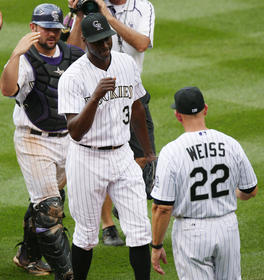 Photo - Colorado Rockies relief pitcher LaTroy Hawkins, center, is congratulated by manager Walt Weiss, right, as catcher Michael McKenry looks on after Hawkins retired the Washington Nationals in the ninth inning of the Rockies' 6-4 victory in a baseball game in Denver, Wednesday, July 23, 2014. (AP Photo)