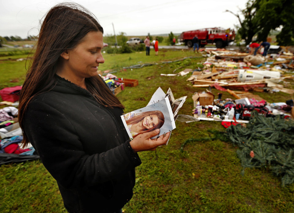 Photo - Christeen Allen finds photographs as friends and family look for mementos and valuables in the wreckage of she and husband Kris's mobil home on Friday, April 29, 2016 in Ninnekah, Okla.  Photo by Steve Sisney, The Oklahoman