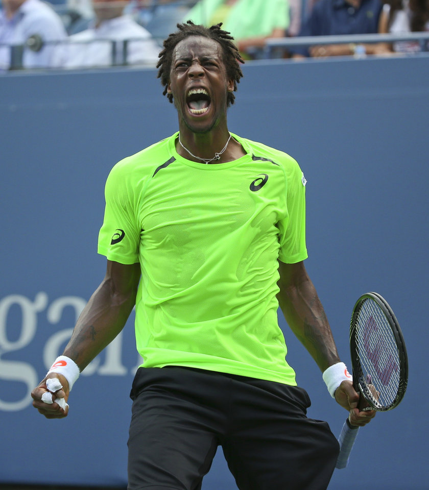 Photo - Gael Monfils, of France, reacts after a shot against Grigor Dimitrov, of Bulgaria, during the fourth round of the 2014 U.S. Open tennis tournament, Tuesday, Sept. 2, 2014, in New York. (AP Photo/Mike Groll)