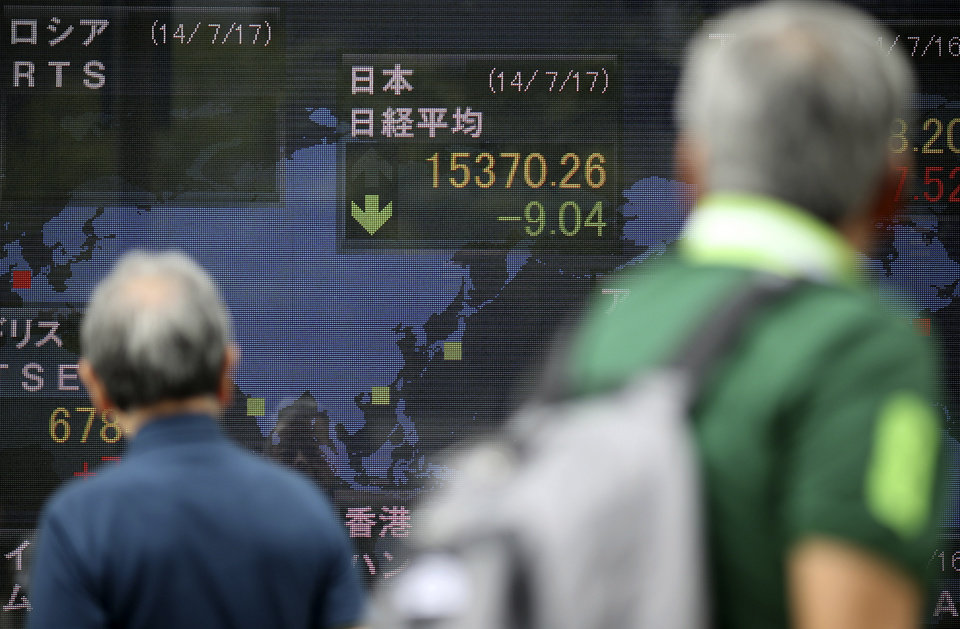 Pedestrians look at an electronic stock board of a securities firm in Tokyo, Thursday, July 17, 2014. Asia's major stock markets mostly posted modest gains Thursday after positive U.S. corporate and economic news underpinned confidence. (AP Photo/Eugene Hoshiko)