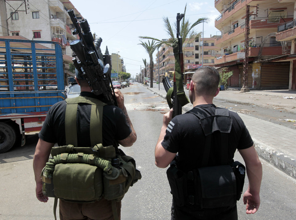 Photo -   Two Sunni gunmen stand in the middle of Syria Street which divides the Sunni and Alawite areas, in the northern port city of Tripoli, Lebanon, Sunday May 13, 2012. Gunfire broke out in the city Saturday and continued through the night primarily between a neighborhood populated by Sunni Muslims who hate Syrian President Bashar Assad and another area with many Assad backers from his Alawite sect. Lebanon's national news agency NNA said one soldier was shot dead by a sniper in the city early Sunday. Another man was found dead on the side of a road while a third died after a shell landed in a residential neighborhood. (AP Photo/Hussein Malla)