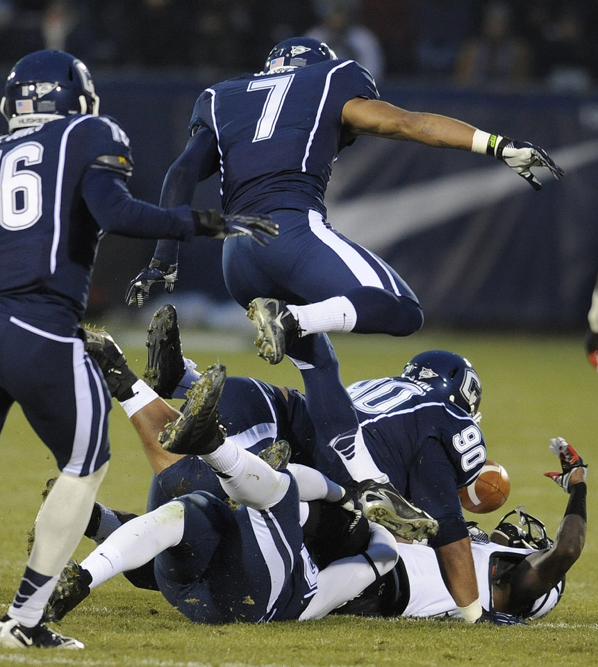 Photo - Connecticut defense causes Cincinnati wide receiver Kenbrell Thompkins (7) to fumble the ball during the first half of an NCAA college football game at Rentschler Field in East Hartford, Conn., Saturday, Dec. 1, 2012. (AP Photo/Jessica Hill)