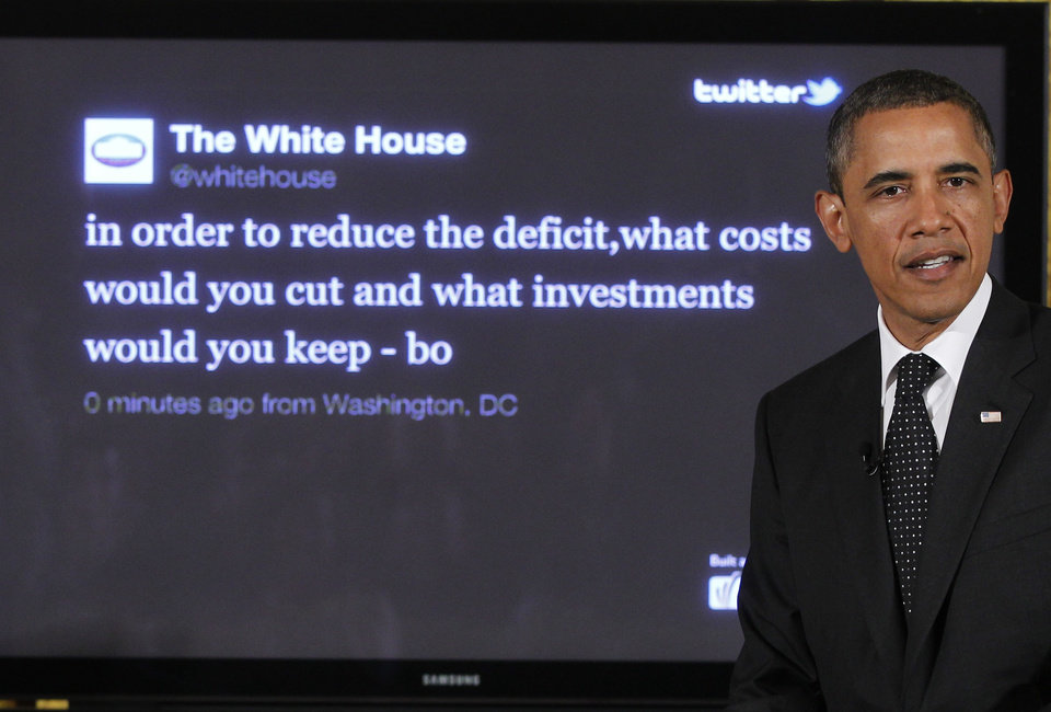 "FILE - In this July 6, 2011, file photo, President Barack Obama sits in front of a screen displaying a question he tweeted during a ""Twitter Town Hall"" in the East Room of the White House in Washington. President Obama is introducing a new hashtag to the fiscal cliff debate. The White House plans to promote (hashtag)My2K on Twitter and other social media — a reference to the estimated $2,200 tax increase that a typical middle-class family of four would see if the Bush tax cuts expire. (AP Photo/Charles Dharapak, File)"
