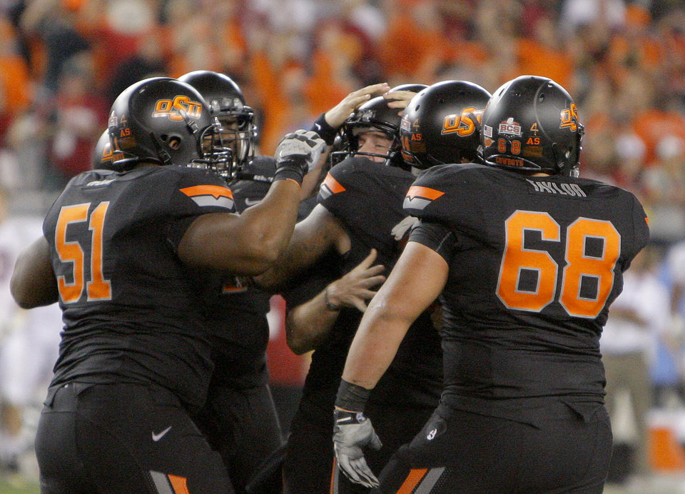 OSU players celebrate with Oklahoma State's Quinn Sharp (13) after kicking the the game-winning field goal during the Fiesta Bowl between the Oklahoma State University Cowboys (OSU) and the Stanford Cardinals at the University of Phoenix Stadium in Glendale, Ariz., Tuesday, Jan. 3, 2012. Photo by Sarah Phipps, The Oklahoman