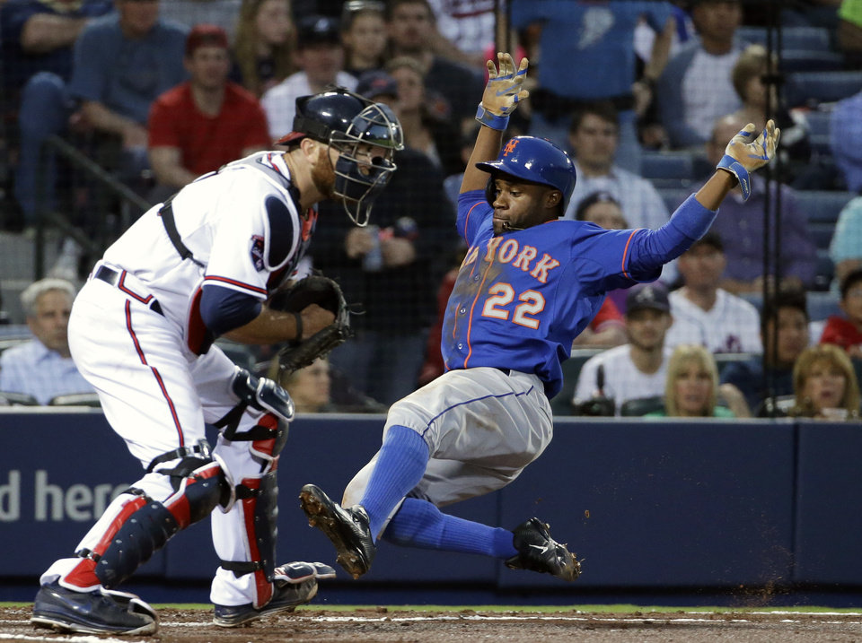 Photo - New York Mets' Eric Young Jr., right, slides into home plate to beat the throw to Atlanta Braves catcher Ryan Doumit to score off a single by teammate David Wright in the third inning of a baseball game, Thursday, April 10, 2014, in Atlanta. (AP Photo/David Goldman)