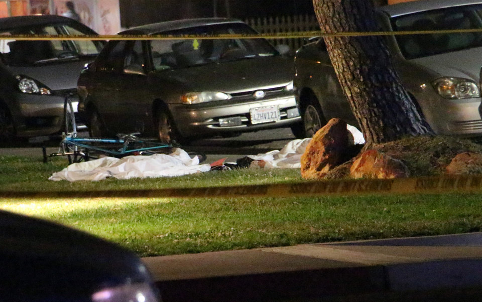Photo - In this image provided by KEYT-TV, bodies are seen covered on the ground after a mass shooting near the campus of the University of Santa Barbara in Isla Vista, Calif., Friday, May 23, 2014.  A drive-by shooter went on a