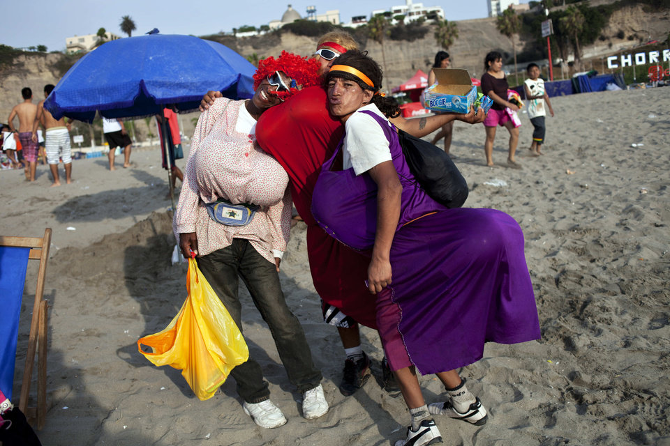 Photo - In this Jan. 17, 2013 photo, performers who also sell candies pose for a photo on Agua Dulce beach in Lima, Peru. While Lima's elite spends its summer weekends in gate beach enclaves south of the Peruvian capital, the working class jams by the thousands on a single municipal beach of grayish-brown sands and gentle waves. The only barrier to entry to Agua Dulce beach is two dollars, the price of bus fare to get there and home. (AP Photo/Rodrigo Abd)