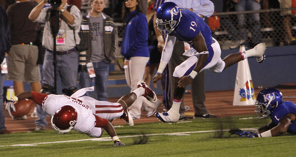 Photo - Oklahoma's Ryan Broyles (85) dives for the end zone in front of Kansas' Victor McBride (19) and Lubbock Smith (1) during the college football game between the University of Oklahoma Sooners (OU) and the University of Kansas Jayhawks (KU) on Sunday, Oct. 16, 2011. in Lawrence, Kan. Photo by Chris Landsberger, The Oklahoman