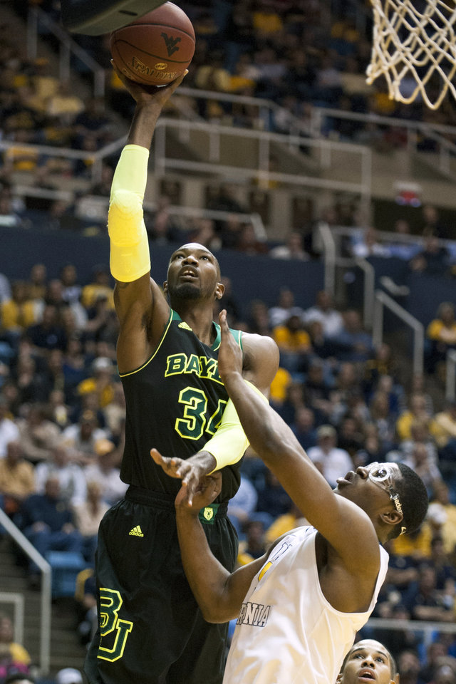 Photo - Baylor's Cory Jefferson, left, looks to shoot over West Virginia's Devin Williams during the first half of an NCAA college basketball game Saturday, Feb. 22, 2014, in Morgantown, W.Va. (AP Photo/Andrew Ferguson)