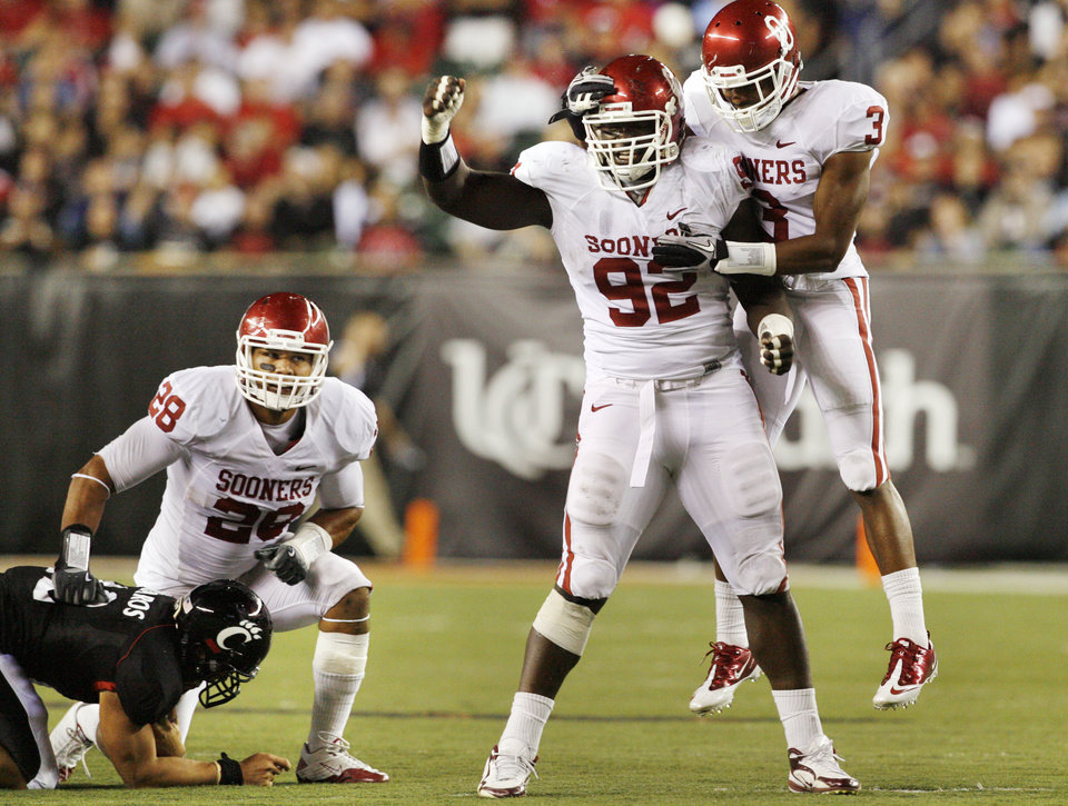 Photo - Sooners Travis Lewis (28), Stacy McGee (92) and Jonathan Nelson (3) celebrate after stopping a quarterback keeper by Zach Collaros (12) during the second half of the college football game between the University of Oklahoma Sooners (OU) and the University of Cincinnati Bearcats (UC) at Paul Brown Stadium on Saturday, Sept. 25, 2010, in Cincinnati, Ohio.   Photo by Steve Sisney, The Oklahoman