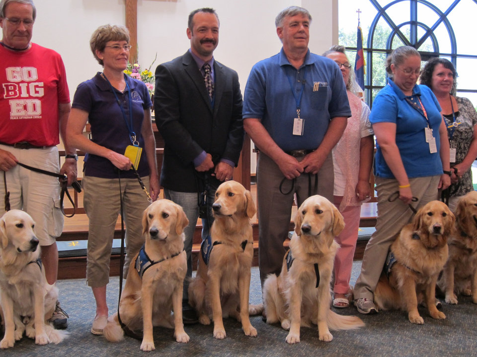 Photo -  All of the Lutheran Church Charities Comfort Dogs attending the recent Passing of the Leash ceremony for Rufus Comfort Dog pose for a picture with their handlers and helpers at St. Mark Lutheran Church, 1501 N Bryant in Edmond. Koey  Keylon, a member of St. Mark, and Rufus Comfort Dog are third from left. Photo by Carla Hinton, The Oklahoman