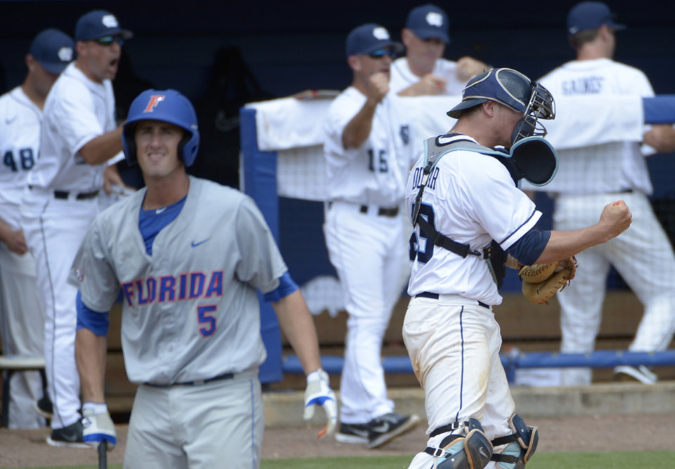 Photo - North Carolina catcher Korey Dunbar, right, pumps his fist after Florida's Zack Powers, left, struck out with the bases loaded to get out of the third inning of an NCAA college baseball regional tournament game in Gainesville, Fla., Saturday, May 31, 2014.(AP Photo/Phelan M. Ebenhack)