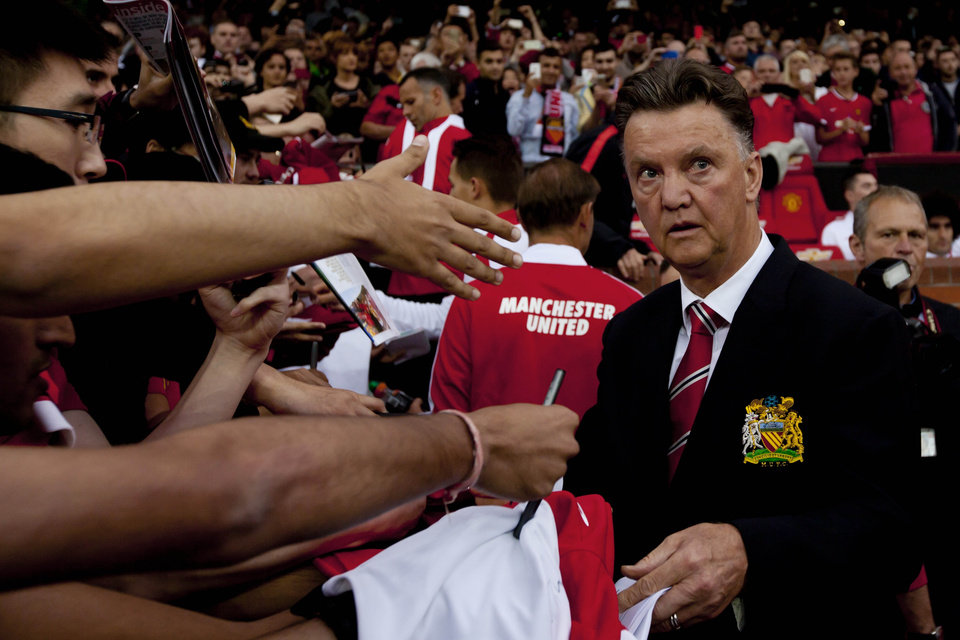 Photo - Manchester United's new manager Louis van Gaal, right, signs autographs as he takes to the touchline before his team's pre season friendly soccer match against Valencia at Old Trafford Stadium, Manchester, England, Tuesday Aug. 12, 2014. (AP Photo/Jon Super)