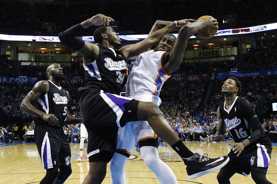 Photo - Oklahoma City Thunder forward Serge Ibaka (9) is fouled by Sacramento Kings forward Jason Thompson (34) during the second quarter of an NBA basketball game in Oklahoma City, Friday, March 28, 2014. (AP Photo/Sue Ogrocki)