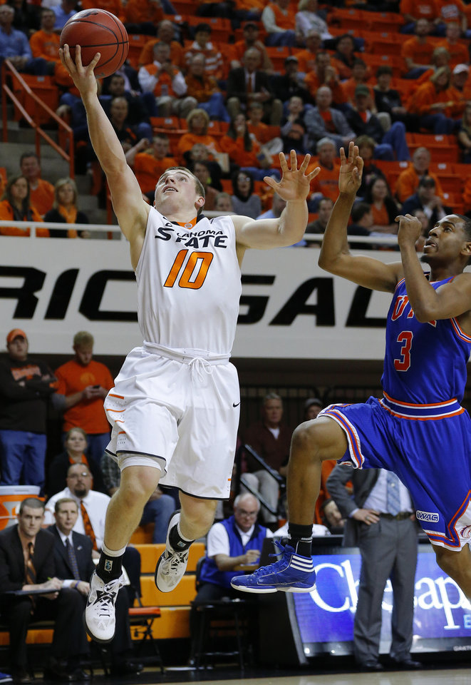 Photo - Oklahoma State's Phil Forte (10) goes past Jamel Outler (3) to the basket during a college basketball game between Oklahoma State University and UT Arlington at Gallagher-Iba Arena in Stillwater, Okla., Wednesday, Dec. 19, 2012. Photo by Bryan Terry, The Oklahoman