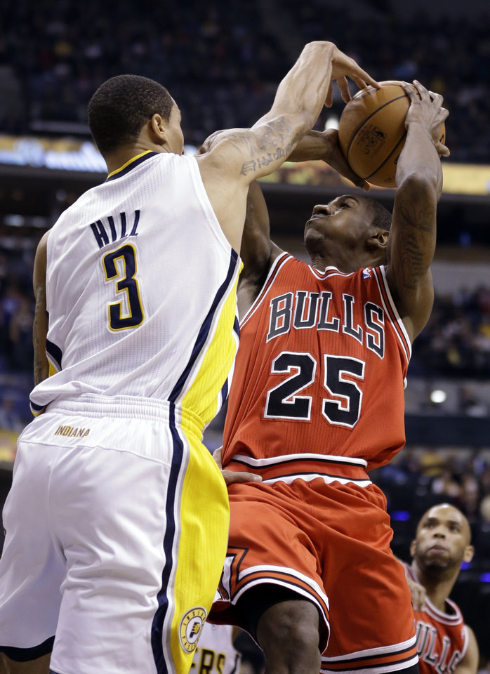 Photo - Indiana Pacers guard George Hill, left, blocks the shot over Chicago Bulls guard Marquis Teague during the first half of an NBA basketball game in Indianapolis, Monday, Feb. 4, 2013. (AP Photo/Michael Conroy)