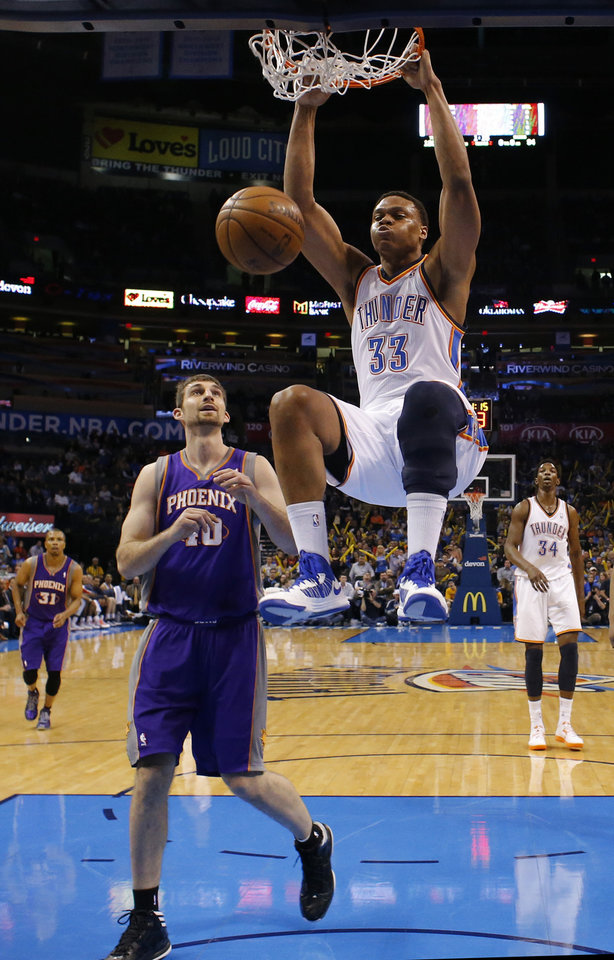 Photo - Oklahoma City's' Daniel Orton (33) dunks over Phoenix 's Luke Zeller (40) during the NBA game between the Oklahoma City Thunder and the Phoenix Suns at theChesapeake Energy Arena, Friday, Feb. 8, 2013.Photo by Sarah Phipps, The Oklahoman