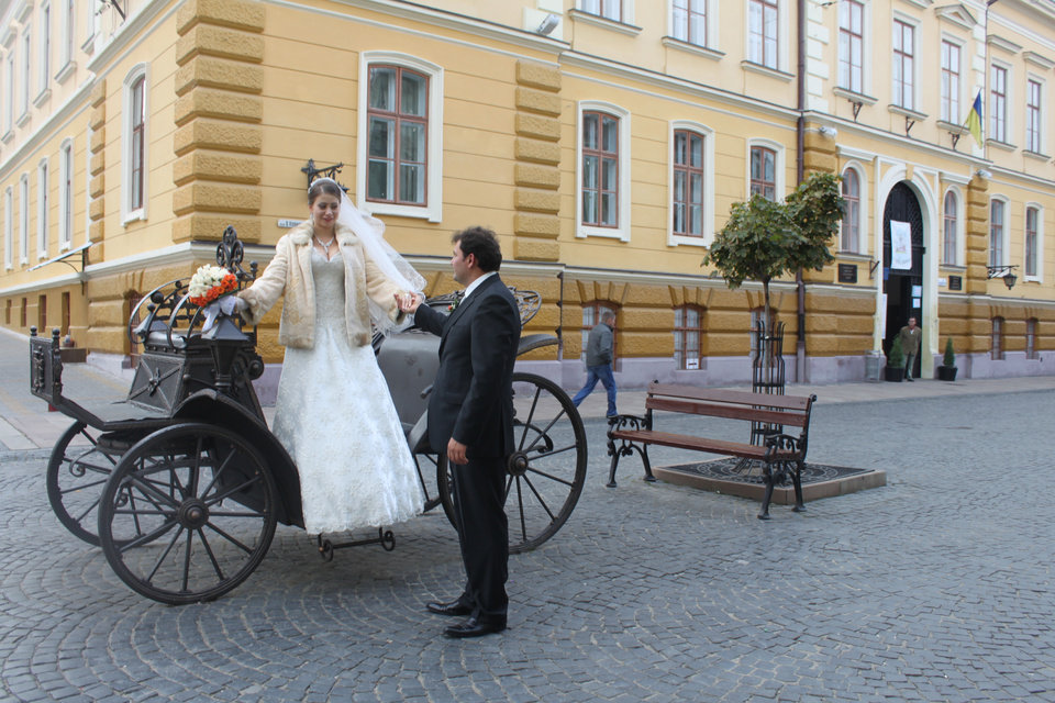 Photo -   In this photo taken on Oct. 21 2012, a bride and a groom prepare for a photo session on the pedestrian-only Olha Kobylianska street in Chernivtsi, a city of 250,000 in southwestern Ukraine. Known as the Little Paris or, alternatively, the Little Vienna of Ukraine, Chernivtsi is a perfect place for a quiet romantic weekend trip and a crash course in the painful history of Europe in the 20th century. (AP Photo/Maria Danilova)