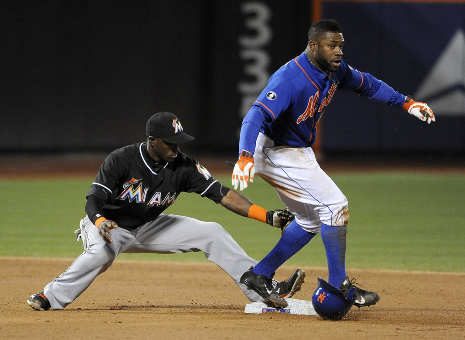 Photo - New York Mets' Eric Young Jr., right, beats the tag by Miami Marlins shortstop Adeiny Hechavarria to safely steal second base in the third inning of a baseball game at Citi Field on Friday, April 25, 2014, in New York. (AP Photo/Kathy Kmonicek)
