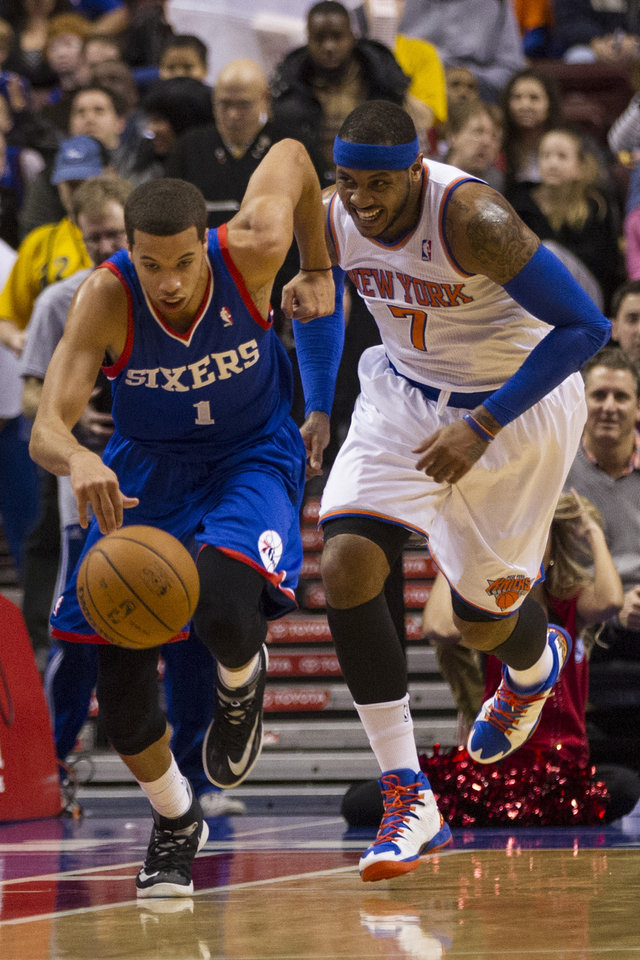 Photo - Philadelphia 76ers' Michael Carter-Williams drives up the court after getting the ball away from New York Knicks' Carmelo Anthony during the first half of an NBA basketball game, Saturday, Jan. 11, 2014, in Philadelphia.  (AP Photo/Chris Szagola)