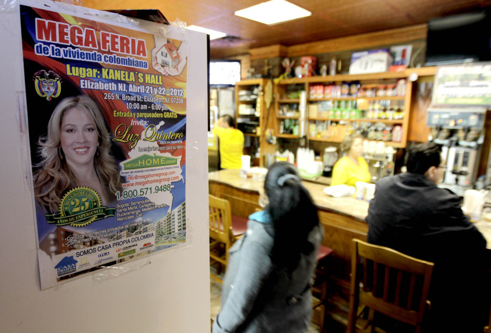 Photo -   A sign promoting an event for Colombian nationals living in the U.S. looking to buy homes hangs inside a bakery in Elizabeth, N.J., Tuesday, May 1, 2012. An information fair being hosted in New York this week by the Colombian government is aimed to for nationals to invest back home. (AP Photo/Julio Cortez)