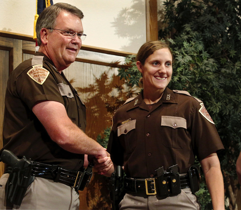 Photo -  New state trooper Sarah Rencken poses with Oklahoma Highway Patrol Chief Kerry Pettingill as she walks across the stage Thursday to receive her diploma and badge. Photo  by Jim Beckel, The Oklahoman.  Jim Beckel