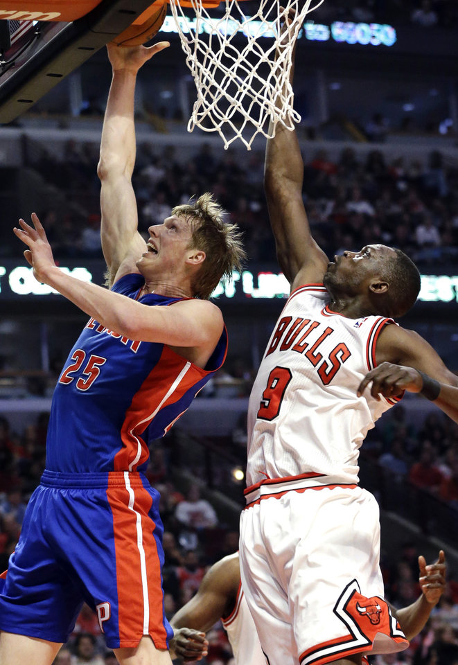 Photo - Detroit Pistons forward Kyle Singler (25) shoots against Chicago Bulls forward Luol Deng during the first half of an NBA basketball game in Chicago, Sunday, March 31, 2013. (AP Photo/Nam Y. Huh)