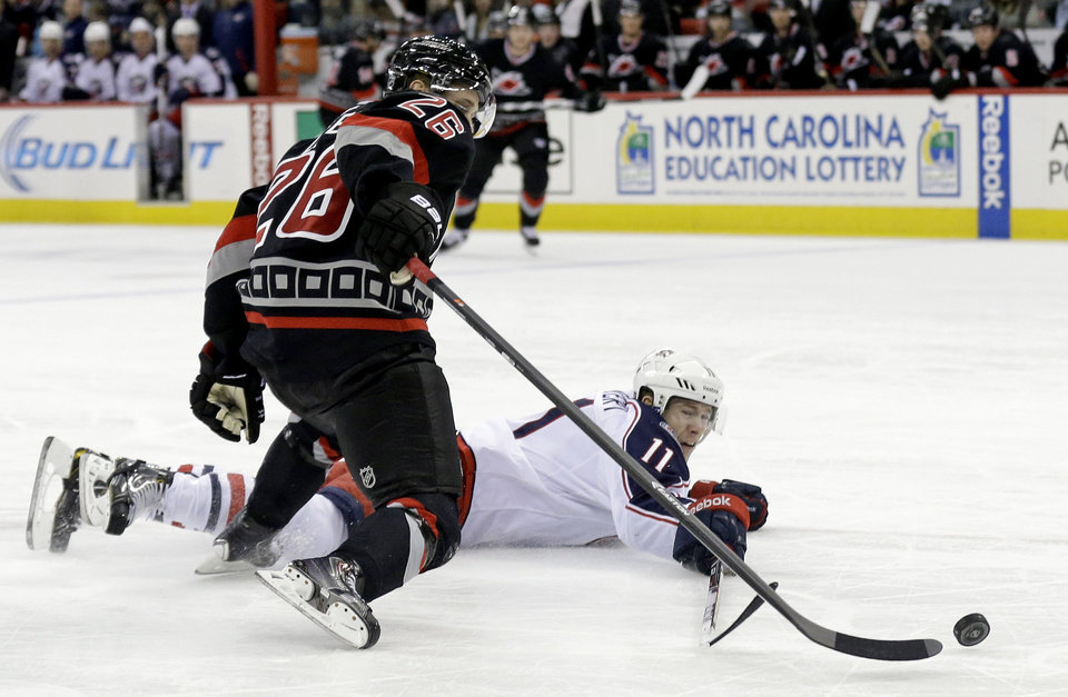 Photo - Carolina Hurricanes' John-Michael Liles (26) and Columbus Blue Jacket's Matt Calvert chase the puck during the first period of an NHL hockey game in Raleigh, N.C., Monday, Jan. 27, 2014. (AP Photo/Gerry Broome)