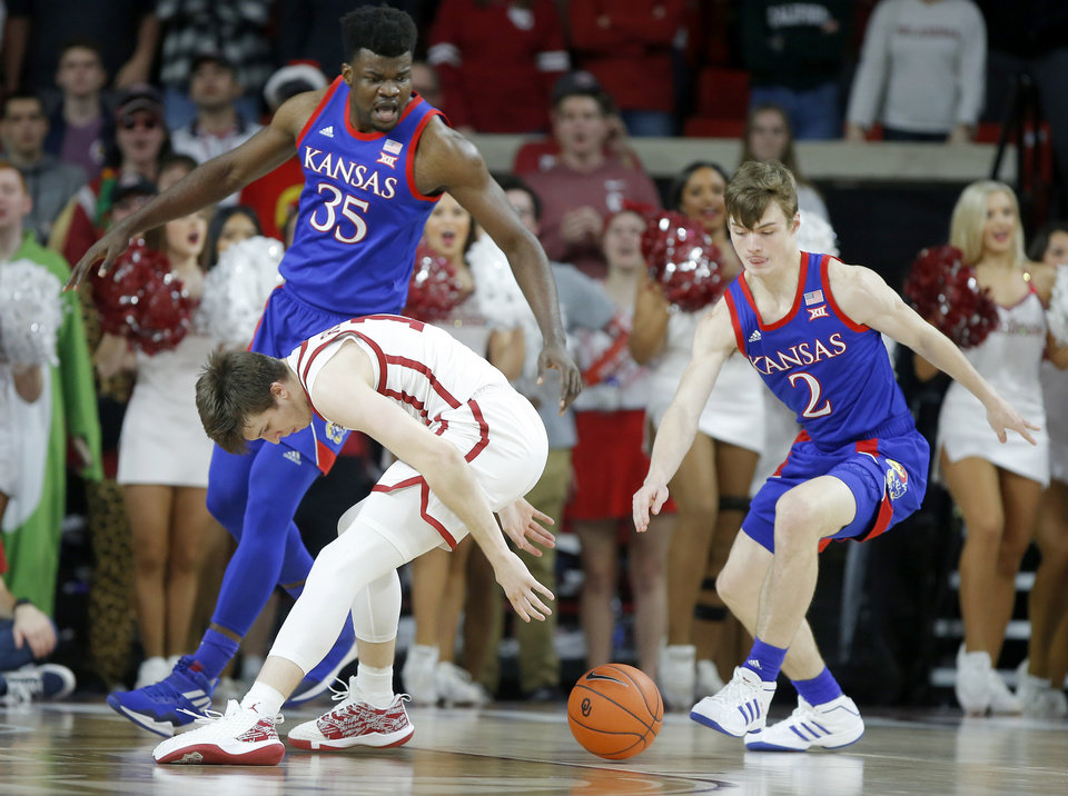 Photo - Oklahoma's Austin Reaves (12) reaches for the ball in front of Kansas' Udoka Azubuike (35) and Christian Braun (2) during an NCAA college basketball game between the University of Oklahoma Sooners (OU) and the University of Kansas Jayhawks at Lloyd Noble Center in Norman, Okla., Tuesday, Jan. 14, 2020. [Bryan Terry/The Oklahoman]