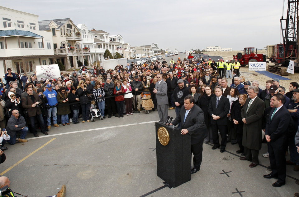 Photo - New Jersey Gov. Chris Christie addresses a large gathering Wednesday, Jan. 9, 2013, as he stands on Ocean Avenue in Belmar, N.J., he helps officials kick off the construction on a 1.3-mile boardwalk to replace the walkway destroyed by Superstorm Sandy in October. The goal is to have it done by May. (AP Photo/Mel Evans)