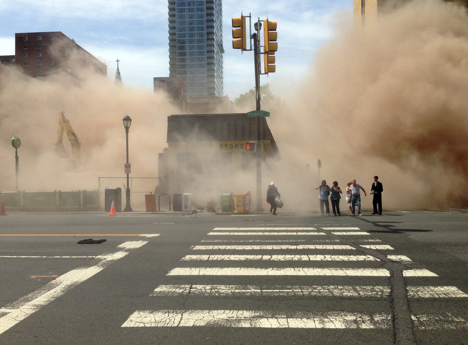 Photo - In this photo provided by Jordan McLaughlin, a dust cloud rises as people run from the scene of a building collapse on the edge of downtown Philadelphia on Wednesday, June 5, 2013. A building that was being torn down collapsed with a thunderous boom, raining bricks on a neighboring thrift store, killing a woman and injuring at least 13 other people in an accident that witnesses said was bound to happen. (AP Photo/Jordan McLaughlin)