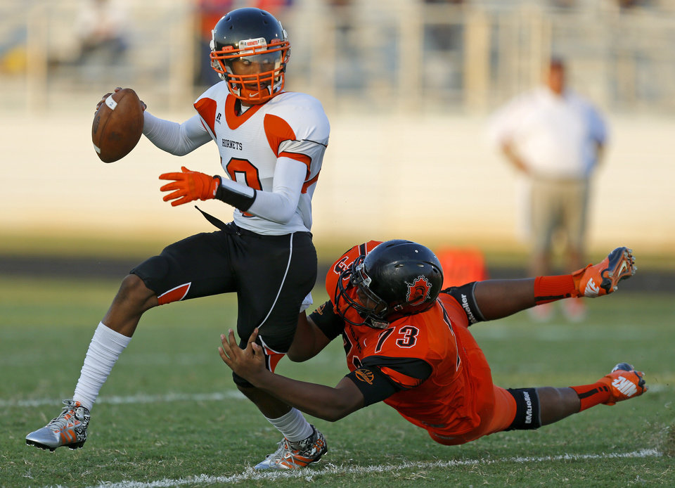 Photo - Mildren Montgomery of Douglass brings down Booker T. Washington's Cordale Grundy during their high school football game at Douglass in Oklahoma City, Friday, September 6, 2013. Photo by Bryan Terry, The Oklahoman