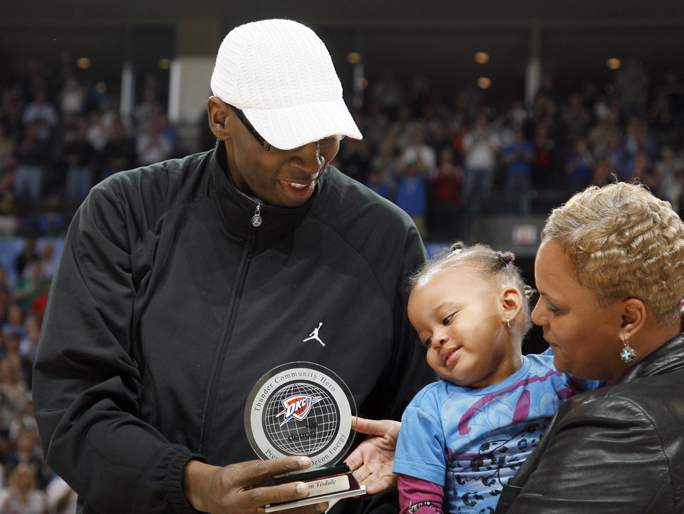 Photo - Wayman Tisdale shows his grand daughter,  Bailey Braxton, and wife Regina, his Thunder Community Hero award during the NBA game between Oklahoma City and San Antonio, Tuesday April 7, 2009, at the Ford Center in  Oklahoma CIty. Photo by Sarah Phipps, The Oklahoma