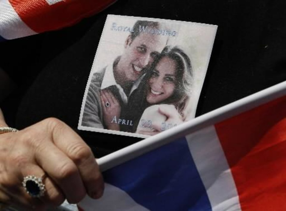 Photo - A picture of Prince William and Kate Middleton is seen on the T-shirt, and a ring similar to that of Kate Middleton's engagement ring worn by a royal fan waiting near Westminster Abbey in London, Thursday, April 28, 2011. Royal enthusiasts are camping out on the pavement to reserve a spot to watch Prince William and Kate Middleton as they arrive to marry in Westminster Abbey on Friday, April 29. (AP Photo/Kirsty Wigglesworth)