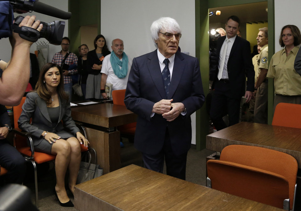 Photo - Formula One boss Bernie Ecclestone, center, arrives besides his wife Fabiana Flosi for his trial in the regional court in Munich, southern Germany, Tuesday, Aug. 5, 2014. Ecclestone is charged with bribery and incitement to breach of trust