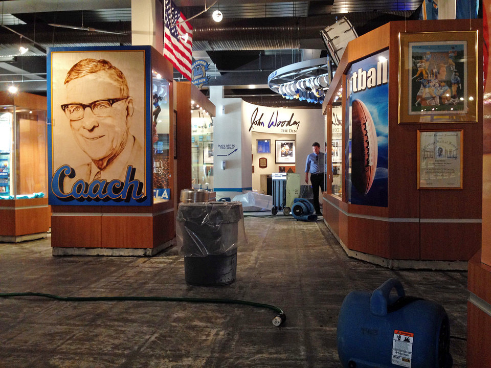 Photo - Carpet has been pulled up and fans dry the floor at the UCLA Athletics Hall of Fame in the J.D. Morgan Center Wednesday, July 30, 2014, after a ruptured 93-year-old water main left the Los Angeles campus awash in 8 million gallons of water in the middle of California's worst drought in decades. The water also flooded the school's storied basketball court less than two years after a major renovation. (AP Photo/Brian Melley)